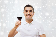 Happy man drinking red wine from glass at home. Profession, drinks, leisure, holidays and people concept - happy man drinking red wine from glass at home over Stock Images