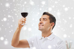 Happy man drinking red wine from glass at home. Profession, drinks, leisure and people concept - happy man drinking red wine from glass at home over snow effect Royalty Free Stock Image
