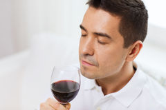 Happy man drinking red wine from glass at home. Profession, drinks, leisure and people concept - happy man drinking and smelling red wine from glass at home Royalty Free Stock Photo