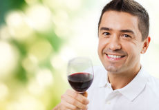 Happy man drinking red wine from glass. Profession, drinks, leisure, holidays and people concept - happy man drinking red wine from glass over green background Stock Image