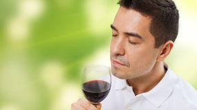 Happy man drinking red wine from glass. Profession, drinks, leisure and people concept - happy man drinking and smelling red wine from glass over green Stock Photography