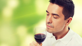 Happy man drinking red wine from glass. Profession, drinks, leisure and people concept - happy man drinking and smelling red wine from glass over green Royalty Free Stock Photo