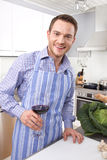 Happy man drinking red wine in the kitchen Royalty Free Stock Image