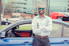 Happy man driver smiling standing by his new sport blue car Stock Photos