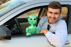 Happy man driving with an alien