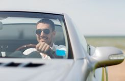 Happy man driving cabriolet car outdoors Stock Images