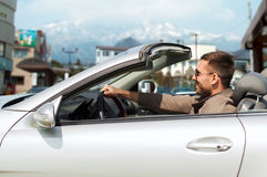 Happy man driving cabriolet car over city in japan Royalty Free Stock Photos