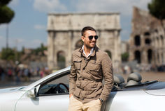 Happy man driving cabriolet car over city of rome Royalty Free Stock Photo