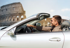 Happy man driving cabriolet car over coliseum Royalty Free Stock Photography