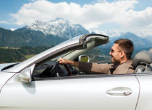 Happy man driving cabriolet car over mountains Royalty Free Stock Photography