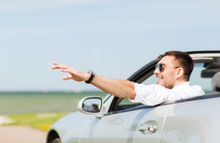 Happy man driving cabriolet car and waving hand Stock Images