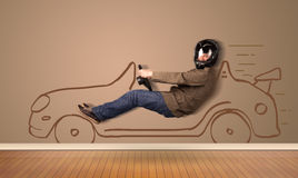 Happy man driving an hand drawn car on the wall Stock Photo