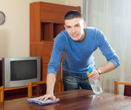 Happy man dusting table with polish Stock Image