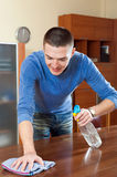 Happy man dusting  table with rag and cleanser at home Royalty Free Stock Photo