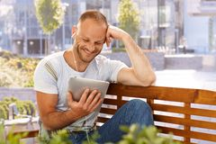 Happy man with e-book reader. Happy man reading e-book outdoors, smiling, using earbuds royalty free stock images