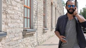 Happy man with earphones over walking in city 11 stock video footage