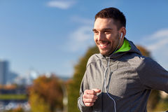 Happy man with earphones running in city. Fitness, sport, people, technology and lifestyle concept - happy man running and listening to music in earphones at Stock Photo