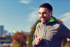 Happy man with earphones running in city Stock Images