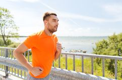 Happy man with earphones running outdoors Royalty Free Stock Images