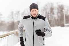 Happy man with earphones and smartphone in winter. Fitness, sport, people, technology and healthy lifestyle concept - young man in earphones with smartphone Stock Images