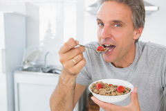Happy man eating cereal for breakfast in kitchen Stock Photography