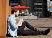 Happy man eating food on lunch break outdoors. Portrait of a happy man eating food on lunch break outdoors stock photos