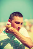 Happy man eating ice cream on beach Royalty Free Stock Images