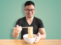 Happy man eating instant noodles. Stock Photography