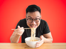 Happy man eating instant noodles. Happy Asian man eats instant noodles with big smile isolated on colour background royalty free stock images