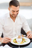 Happy man eating salad for dinner at restaurant Royalty Free Stock Photography