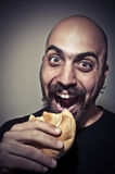 Happy man eating a sandwich Stock Image