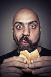 Happy man eating a sandwich Royalty Free Stock Image