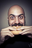 Happy man eating a sandwich Royalty Free Stock Images