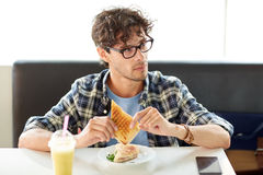 Happy man eating sandwich at cafe for lunch Royalty Free Stock Image