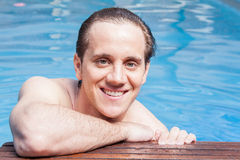 Happy man in the edge of the pool Royalty Free Stock Photography