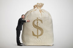 Happy man embracing big bag with money Royalty Free Stock Image