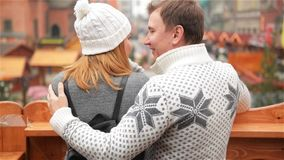 Happy Man Embracing Smiling Woman on Christmas Market Background. Couple in Love Talking about Something Looking on stock footage