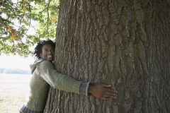 Happy Man Embracing Tree Trunk At Park Royalty Free Stock Photography