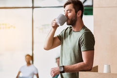 Happy man enjoying hit beverage at workplace. Relaxed young male worker is drinking coffee with enjoyment. He is standing in office. Copy space Stock Photo