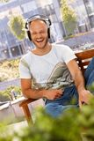 Happy man enjoying music outdoors Stock Images