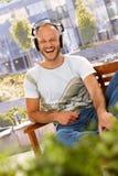 Happy man enjoying music outdoors Stock Images