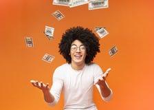 Happy man enjoying the rain of money. Happy curly black guy enjoying rain of money, orange studio background royalty free stock photography