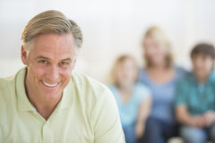 Happy Man With Family Sitting In Background At Home Royalty Free Stock Image