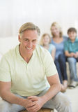 Happy Man With Family Sitting In Background At Home Royalty Free Stock Images