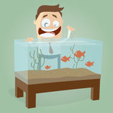 Happy man feeding aquarium fishes Stock Photo