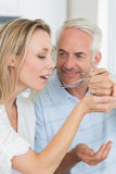 Happy man feeding his partner a spoon of the dinner Royalty Free Stock Photography