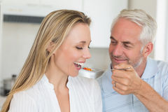 Happy man feeding his partner a spoon of vegetables Stock Photography