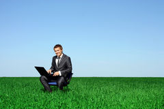 Happy man on the field with laptop stock photography