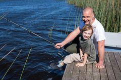 Happy man fishing with his son Royalty Free Stock Photography