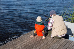 Happy man fishing with his son Royalty Free Stock Image